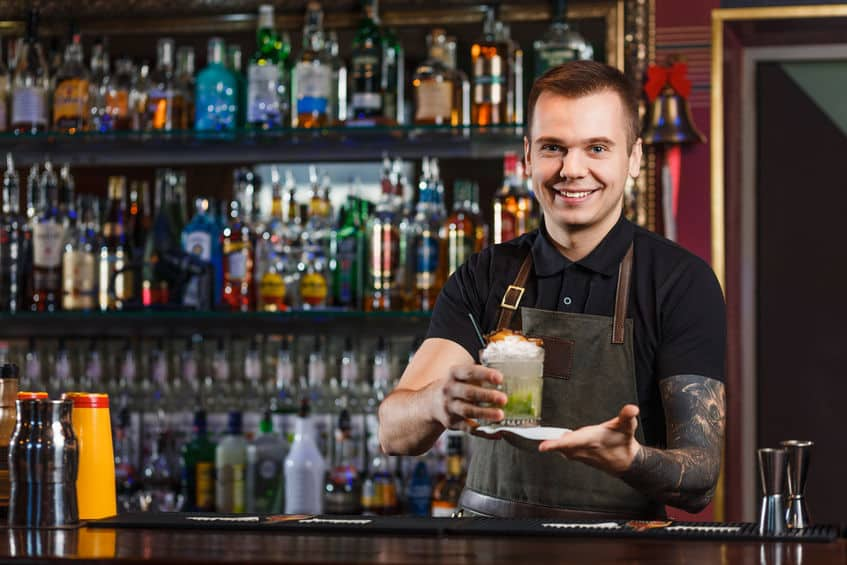 This bartender shows a confident smile, which is a big part of the job, that only comes with practical experience behind the bar. (© aksakalko/123RF photo)