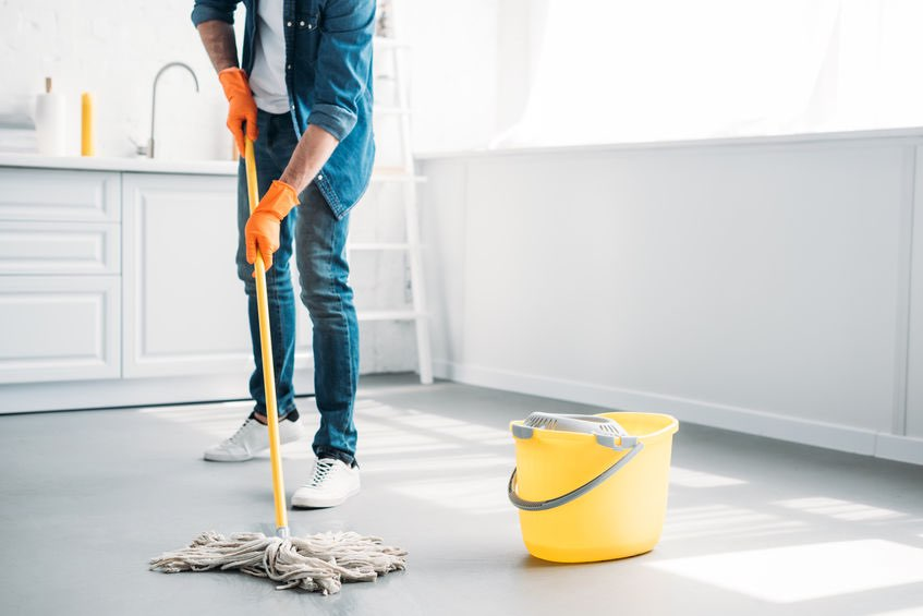 A photo of a man mopping the floor, showing the importance of cleanliness in the home bar. (© lightfieldstudios/123RF photo)
